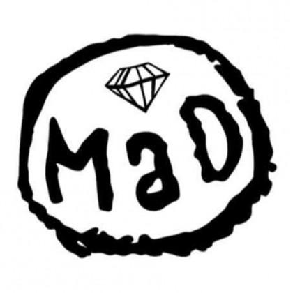 Karkeasti piirretty ympyrä, jonka sisällä piirretty timantti ja teksti: MAD.